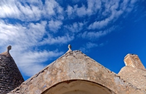 An abandoned trullo below blue autumn skies.