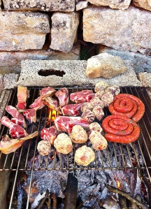 Grilled meats over an improvised grill for a Sunday lunch all'aperto.