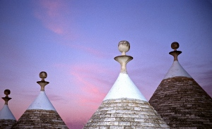 The summer sun sets over the pinnacles of a set of cone-shaped stone houses called trulli.