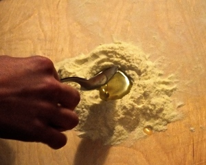 Making a well with flour to hold the liquid ingredients as you gently mix the purcidd dough with your hands.