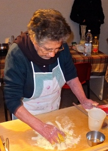 Nonna Maria mixes purcidd dough with her hands on a wooden pasta board.