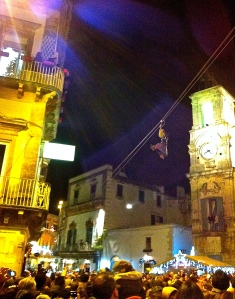 The befana flies through the sky from the bell tower in Martina Franca's basilica distributing candy to the crowd below.