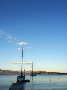 As twilight approaches, sailboats appear to float on the glassy surface of the Ionian sea in this quiet bay on Paxos.