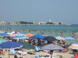 Tightly packed beach umbrellas, shallow, warm water and clear blue skies characterize the Adriatic beach scene in summer.