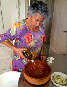Mrs. Speranza sprinkles the sea salt into the bottom of the terracotta dish.