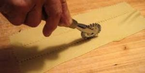Use a pastry wheel to cut strips of dough from the thin pasta strips than emerged from the pasta machine.