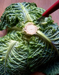 After peeling off the loose outer leaves of the head of cabbage and reserving them, core the cabbage by turning it upside down and inserting a knife at an angle deep alongside the edges of the core.