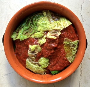 The cabbage rolls, covered in tomato sauce and extra cabbage leaves, are ready to go into the oven.